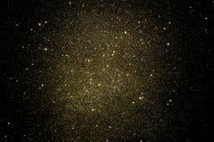 Guld blänker på en svart bakgrund arkivfoto