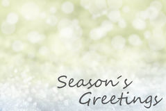 Guld- Bokeh julbakgrund, snö, text kryddar hälsningar Arkivfoto