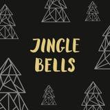Guld- bokstäverklirrklockor och triangelgranträd på svarta lodisar Arkivfoto