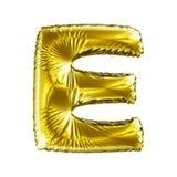 Guld- bokstav E som göras av den isolerade uppblåsbara ballongen på vit bakgrund Fotografering för Bildbyråer