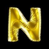 Guld- bokstav N som göras av den isolerade uppblåsbara ballongen på svart bakgrund Royaltyfria Bilder