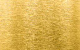 Guld borstad metalltextur eller bakgrund Royaltyfria Bilder