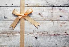 Guld- bow med woodgraincopyspace Fotografering för Bildbyråer