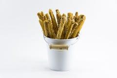 Guld- brunt för Breadstick i den vita behållaren som isoleras på vit bakgrund Royaltyfri Foto