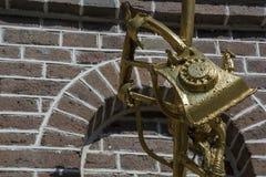 Guld- bruten telefon som skulptur med tegelstenväggen som bakgrund Fotografering för Bildbyråer