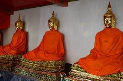 Guld- buddha bild med den gula ämbetsdräkten Fotografering för Bildbyråer