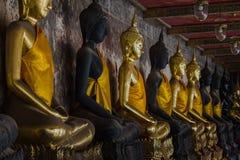 Guld- Buddha bredvid gamla väggar i thailändska tempel arkivfoto