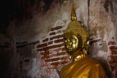 Guld- Buddha bredvid gamla väggar i thailändska tempel arkivbild