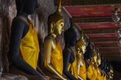 Guld- Buddha bredvid gamla väggar i thailändska tempel arkivfoton