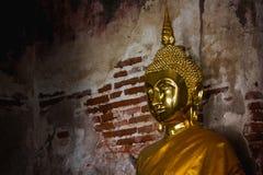 Guld- Buddha bredvid gamla väggar i thailändska tempel arkivbilder