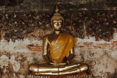 Guld- Buddha bredvid gamla väggar i thailändska tempel fotografering för bildbyråer