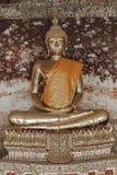 Guld- Buddha bredvid gamla väggar i thailändska tempel royaltyfria foton