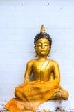 Guld- Buddha på det vita bakgrundstegelstenkvarteret Arkivbild