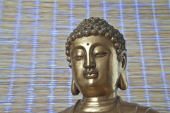 Guld- Buddha som ner ser Royaltyfria Bilder