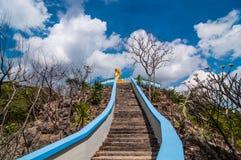 Guld- Buddhastaty för trappa upp till på berget Arkivfoton