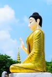 Guld- Buddhastaty i blå himmel royaltyfri bild