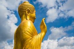 Guld- Buddhastaty på bakgrund för blå himmel Arkivfoto