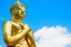 Guld- Buddhastaty på bakgrund för blå himmel Royaltyfri Foto