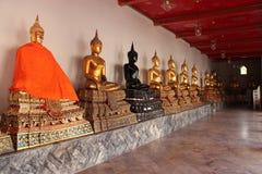 Guld- Buddhastatyer dekorerar ett galleri av en tempel (Thailand) arkivbild