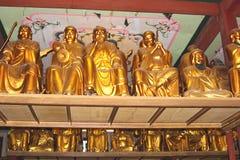 Guld- Buddhastatyer i den Hualin templet, den äldsta templet i Guangzhou i Kina Arkivbild