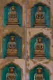 Guld- Buddhastatyer längs väggen i inre av Linhen Royaltyfri Fotografi