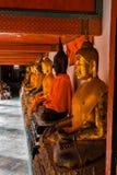 Guld- Buddhastatyer med apelsinen sätter band Surat Thani Thailand fotografering för bildbyråer