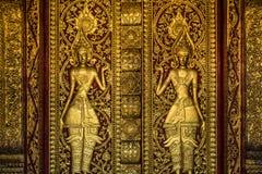 Guld- buddistisk dörrskulptur arkivbilder
