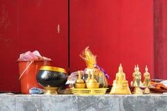 Guld- bunkar och statyetter av Buddha förlades på kanten av ett fönster i en tempel (Thailand) royaltyfri fotografi