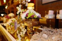 Guld- bunke med härliga blommor, romantisk garnering royaltyfria foton