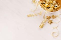 Guld- bunke med julstjärnor, bollar, band på det vita wood brädet, kopieringsutrymme Festlig xmas-bakgrund arkivfoto