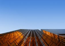 Guld- byggnad med blå himmel Windows exponeringsglas av det moderna kontoret sk royaltyfria bilder