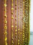 Guld- chimes som dekorerar dörrgardinen, inställde och grund avdelning royaltyfri bild