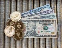 Guld- Crypto mynt Ethereum ETH Papper fakturerar oss dollar Metallmynt läggas ut i slät bakgrund till varandra, närbildsikten Arkivfoton