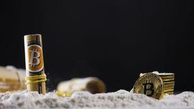 Guld- crypto mynt faller ner på pulver och rullar arkivfilmer
