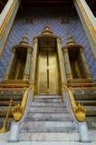 Guld- dörrar och naga på ingången till det Phra Mondop arkivet på den historiska storslagna slotten i Bangkok, Thailand Arkivbild