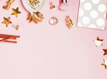 Guld- dekor och kvinnlig tillbehör på den rosa bakgrunden royaltyfri bild