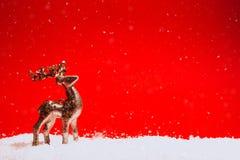 Guld- dekorativ hjort står på röd bakgrund med snö royaltyfri bild