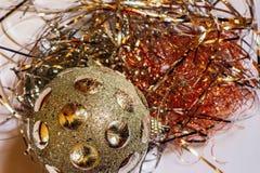 Guld- dekorativ jul klumpa ihop sig på den metalliska röda och guld- tråden på vit bakgrund Arkivfoton