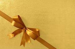 Guld- diagonalt band för hörngåvapilbåge, skinande metallisk foliepappersbakgrund Royaltyfri Fotografi