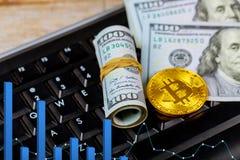 Guld- dogecoincryptocurrencymynt som ligger på en hög av kontanta sedlar för US dollar, guld- Bitcoin tangentbord Arkivfoto