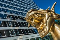Guld- drake och byggnad Arkivbild