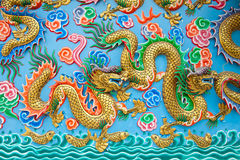 Guld- drakestaty på den blåa väggen arkivfoton