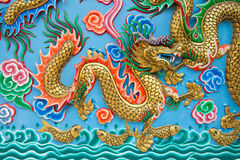 Guld- drakestaty på den blåa väggen royaltyfri fotografi