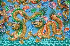Guld- drakestaty på den blåa väggen royaltyfri foto