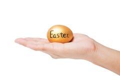 Guld- easter ägg i hand Arkivfoto