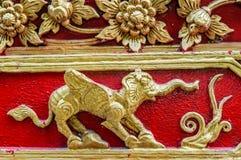 Guld- elefant med blommor, vingar och jordluckrare på den röda väggen Arkivbilder