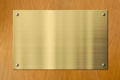 Guld- eller mässingsmetallplatta på wood bakgrund Royaltyfri Fotografi