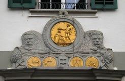 Guld- emblem på den yttre väggen av en byggnad på Muehlenplatz i Lucerne royaltyfria bilder