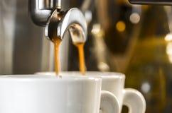 Guld- espresso som flödar in i koppar Arkivbilder
