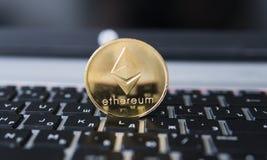Guld- Ethereum mynt på en bärbar dator Ethereum crypto valuta på ett bärbar datorsvarttangentbord Digital pengar och faktiskt Royaltyfria Foton